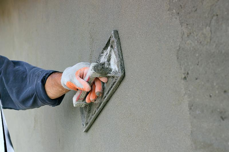 Mans hand plastering wall